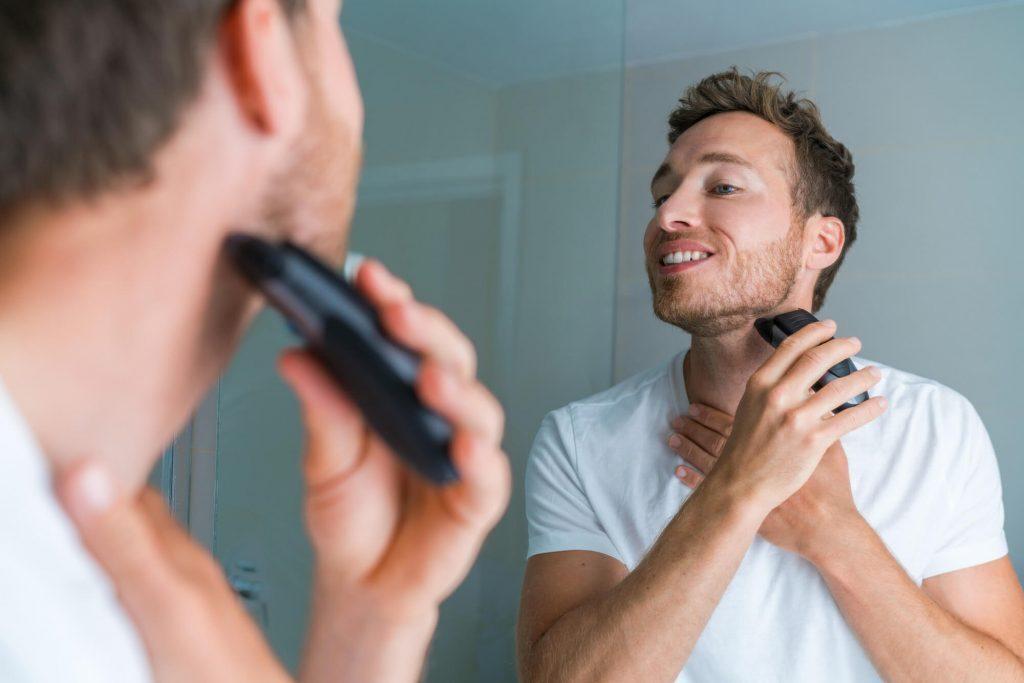 Man trimming his beard in mirror