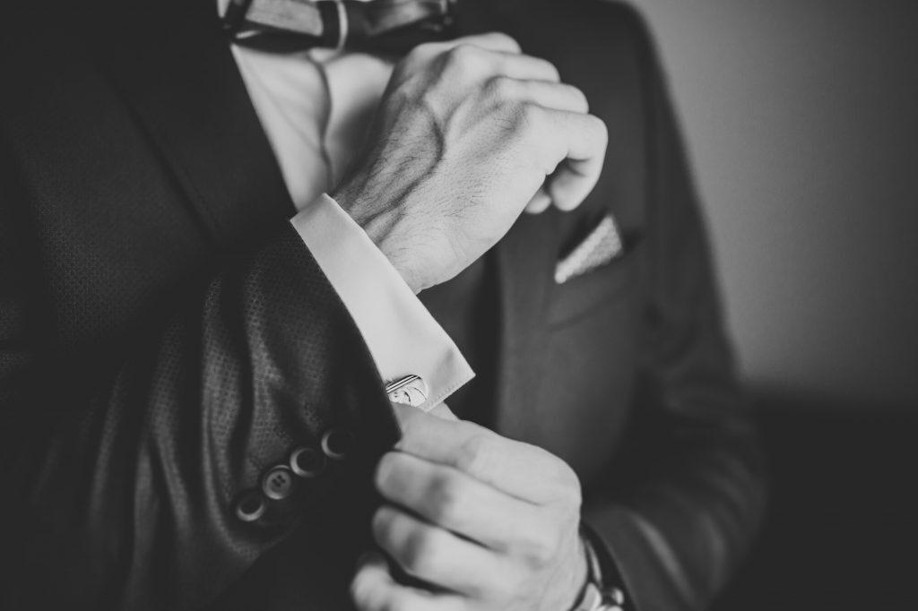 Man wearing a fancy tuxedo, adjusting cufflinks
