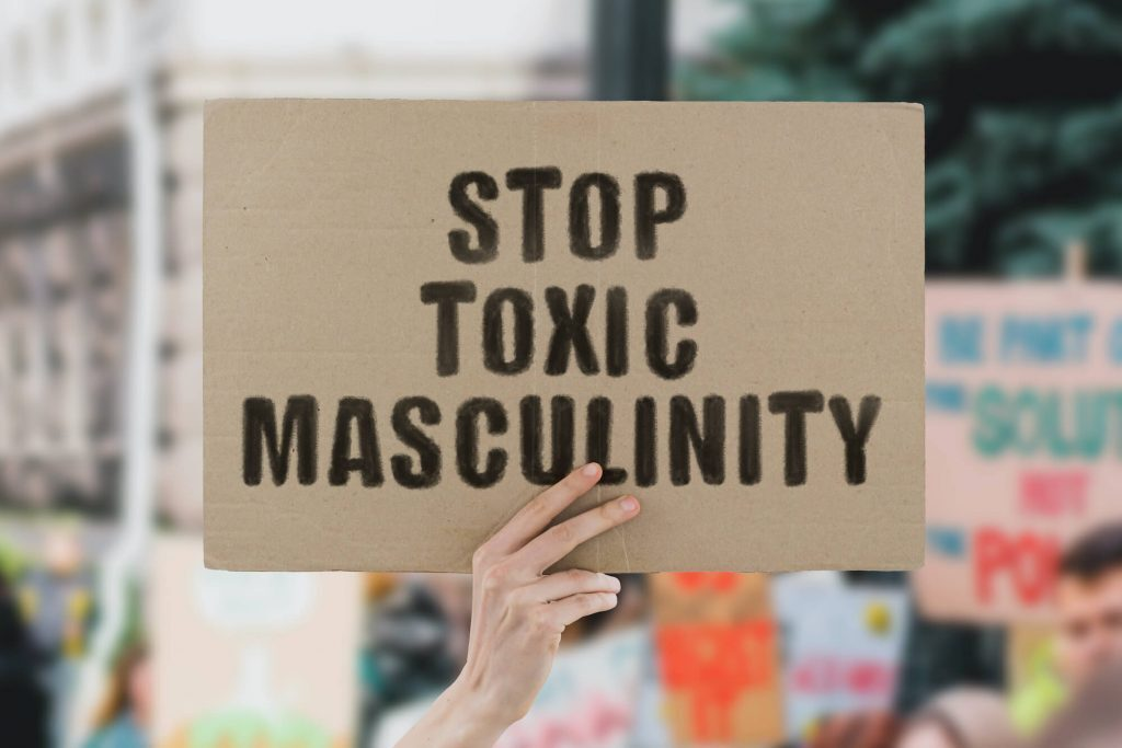 Man holding sign that says stop toxic masculinity