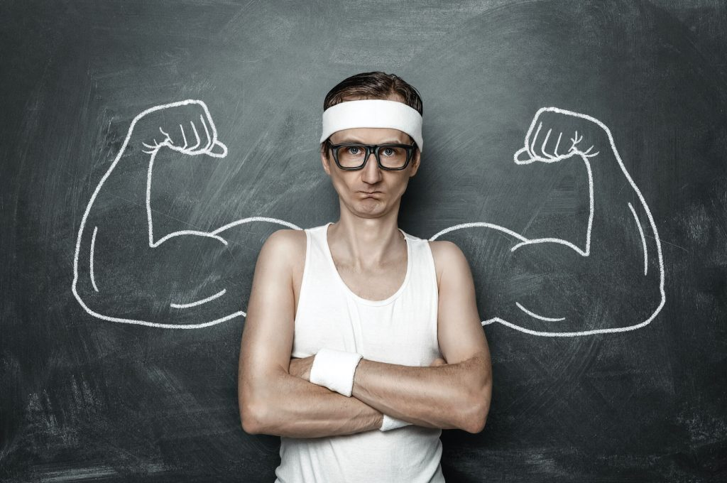 Skinny guys standing in front of chalk board with buff arms drawn on behind him