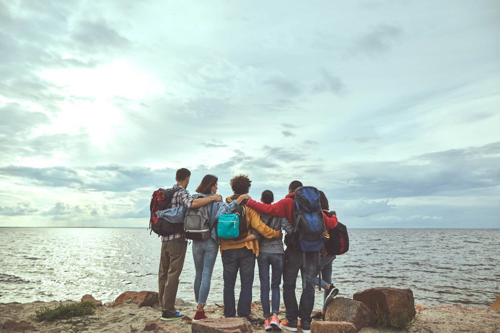 Gang of friends huddled together looking at the ocean