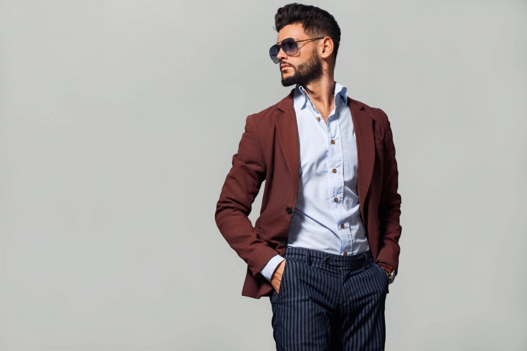 Man in Oxford shirt, maroon blazer, pinstripe dress pants, and sunglasses