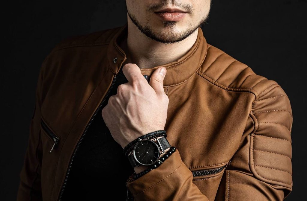 Man wearing watch and brown biker jacket