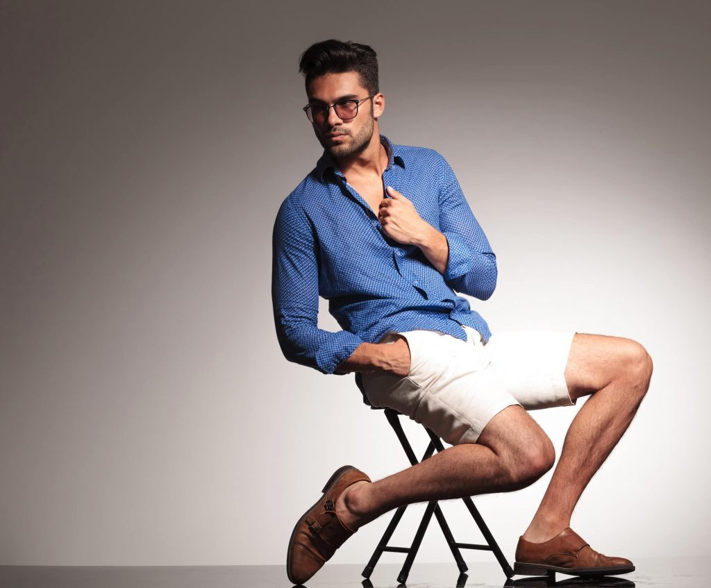 Man in sunglasses, chino shorts and button down shirt sitting on chair