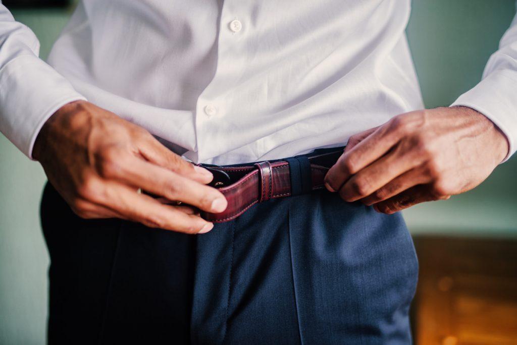 Man putting a belt on his dress pants