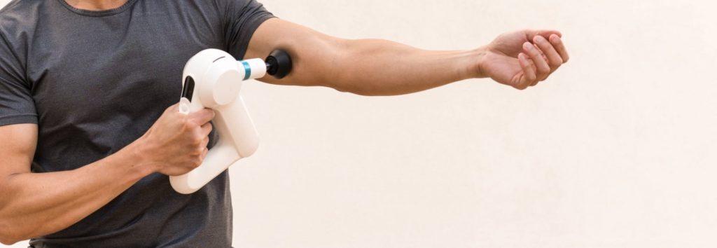 Man uses Theragun Pro massage gun on bicep muscle