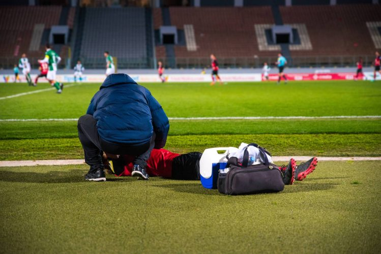 A sports doctor cares for the football player (1)