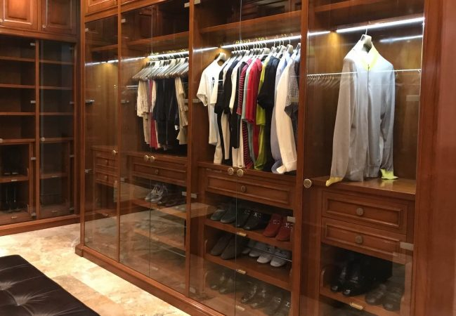 Men's luxury walk-in closet with hanging clothes